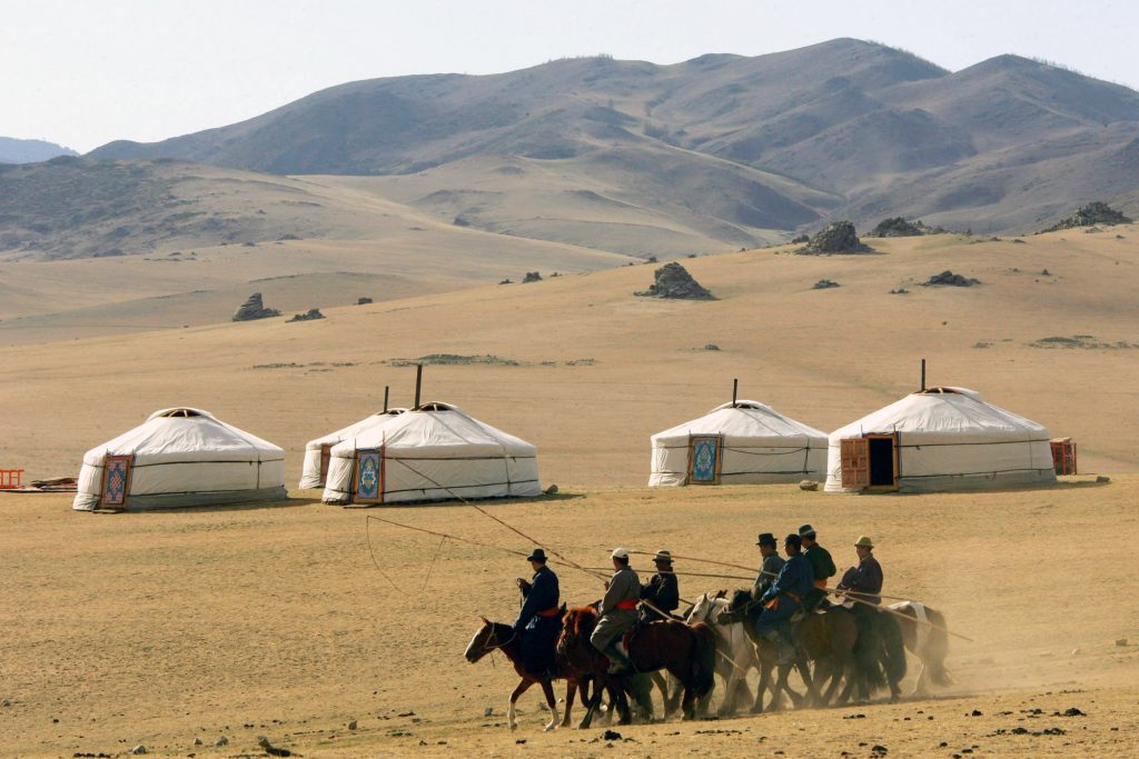 Mongolian horsemen ride past a row of traditional felt tents near Kharkorin.